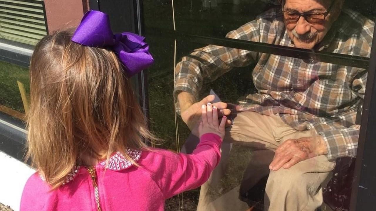 St. Louis άνθρωπος γιορτάζει 103η γενέθλια με την οικογένεια μέσα από μια γυάλινη πόρτα